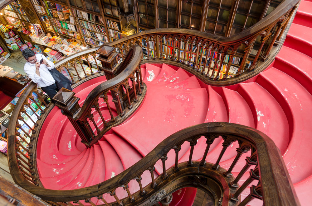 An unidentified man takes photo of the staircase at the Lello & Irmao bookstore. Photo: Shutterstock