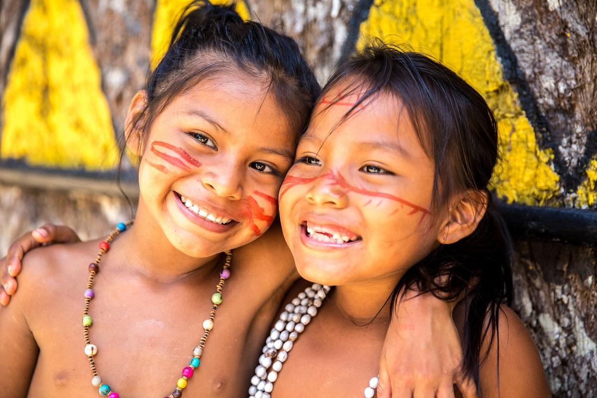 Cute Brazilian indians paying in Amazon, Brazil. Photo:  Frazao Production/Shutterstock