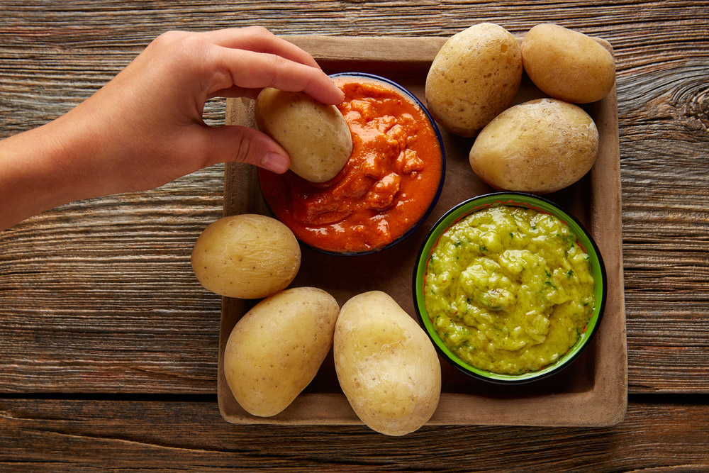 Papas arrugas al mojo, wrinkled potatoes with green and red sauces.