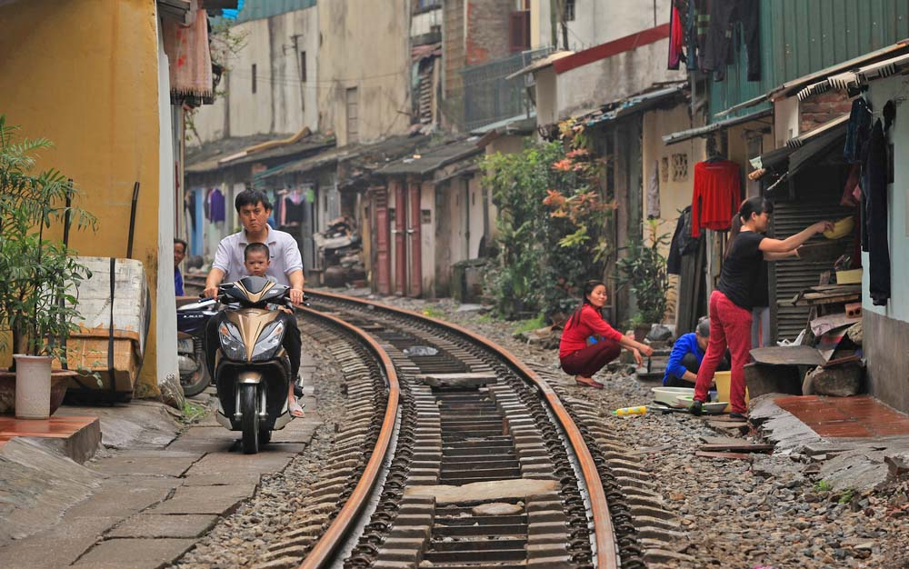 Everday life and typical houses on the railway track in Hanoi.