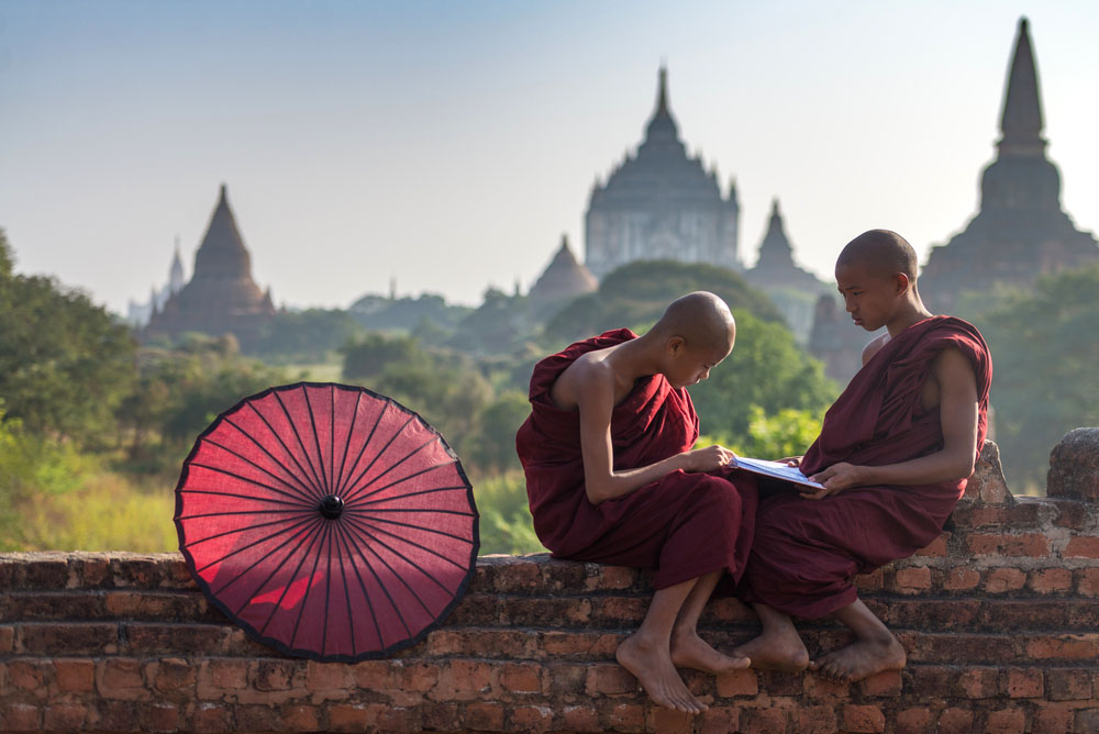Couple of novice read a book on monastery's wall with field of ancient pagoda background in Old Bagan. Photo: Shutterstock