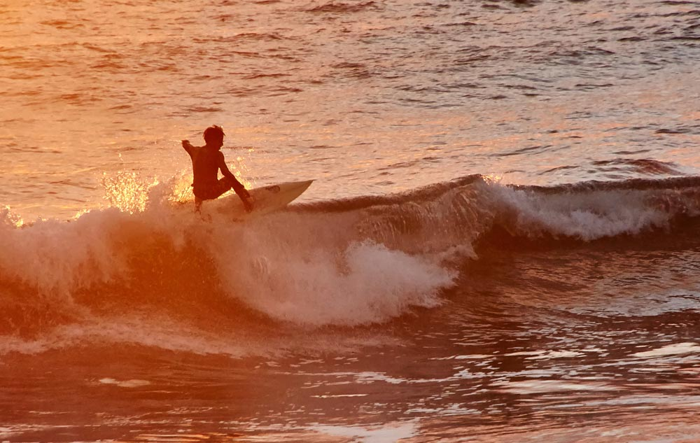 Surfer riding a wave at sunset in Ecuador.