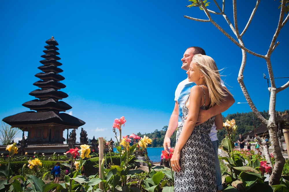 Honeymoon couple near the Balinese temple at beratan lake, Bali. Photo: Pavel Ilyukhin/Shutterstock