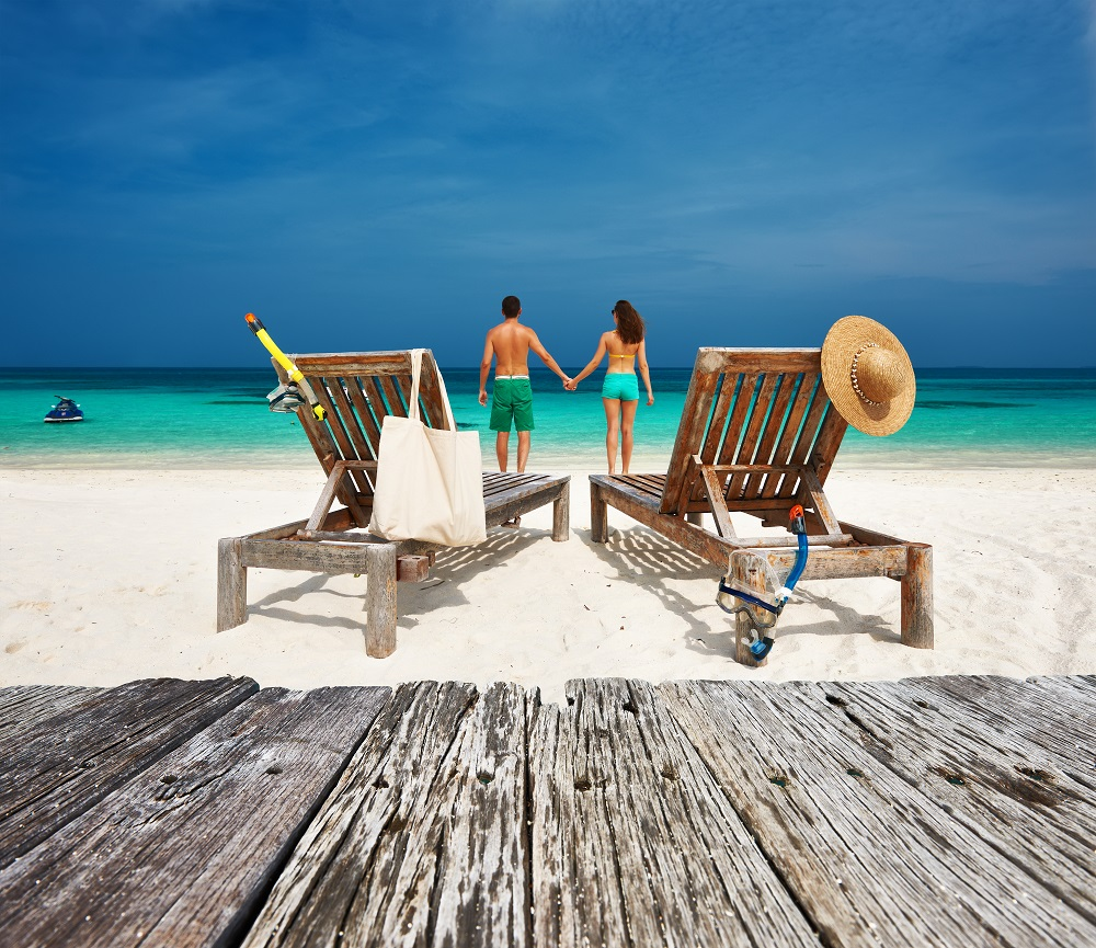 Couple relax on a tropical beach at Maldives. Photo: haveseen/Shutterstock