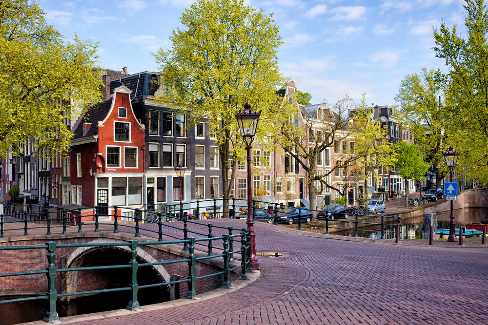 Picturesque traditional Dutch houses and bridge on the Reguliersgracht canal in Amsterdam. Photo: Shutterstock