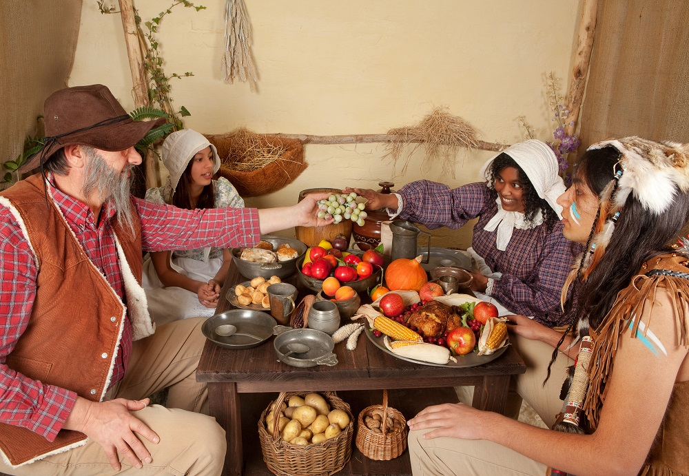Reenactment scene of the first Thanksgiving Dinner in Plymouth in 1621 with a Pilgrim family and a Wampanoag Indian. Photo: Anneka/Shutterstock