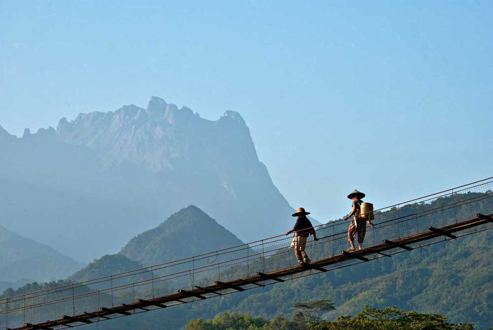 Walking on a suspension bridge on an early morning, with Mount Kinabalu as background in Malaysia. Photo: Shutterstock
