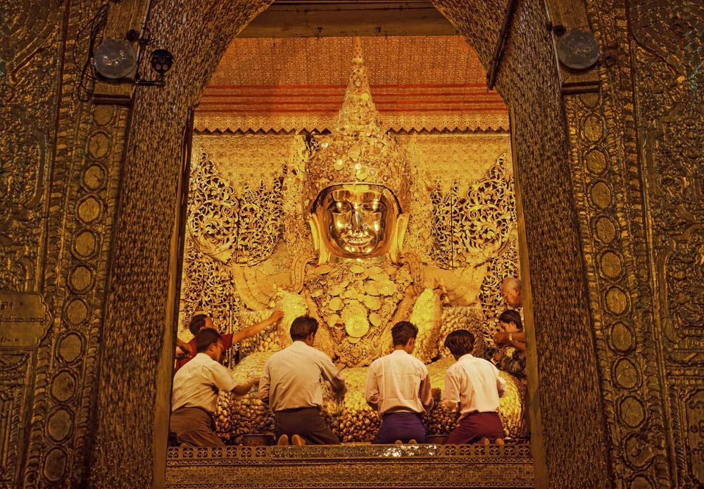 Burmese believers worship Buddha statue pasting gold leaf petals in Maha Muni Pagoda. Photo: Shutterstock