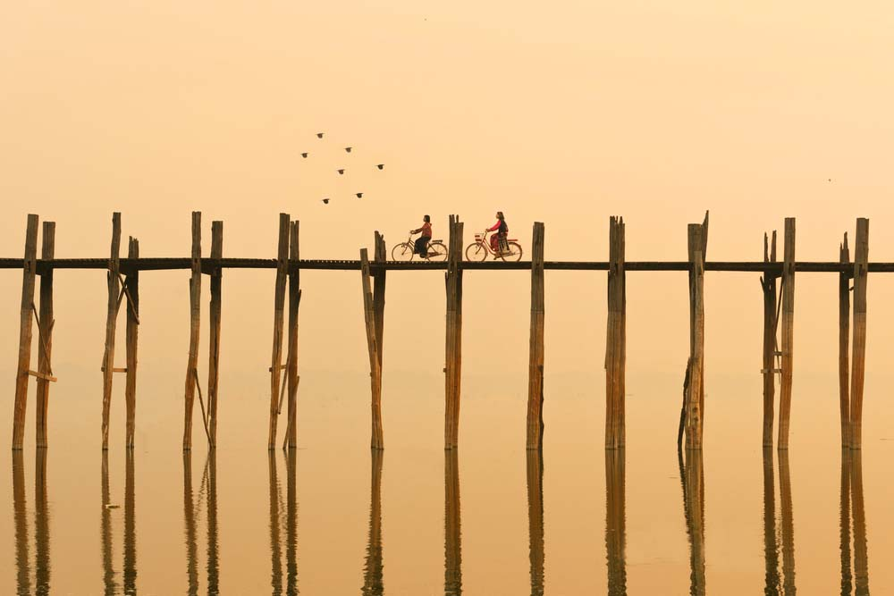 Crossing the U Bein Bridge as the sun rises is one of our favourite things to do in Mandalay.