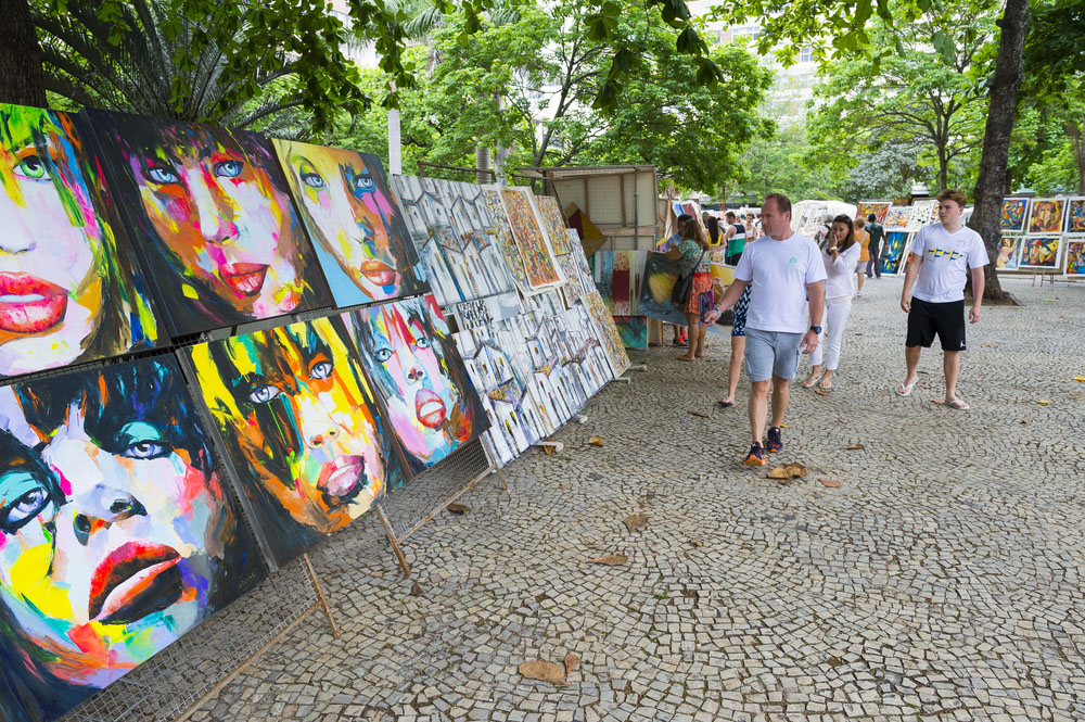 Shoppers look at art displayed at the outdoor Hippie Fair market in General Osorio Plaza in Ipanema.