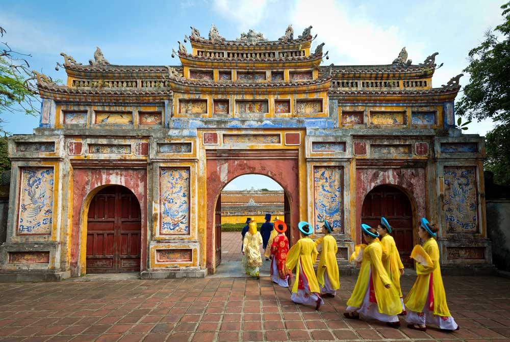 People in traditional costumes walk under an archway in the Imperial City of Hue, Vietnam. Photo: Shutterstock