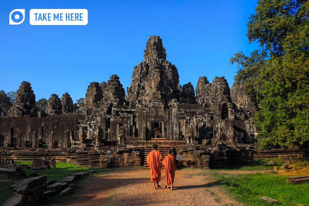 The monks alongside the ancient stone faces of Bayon temple, Angkor.