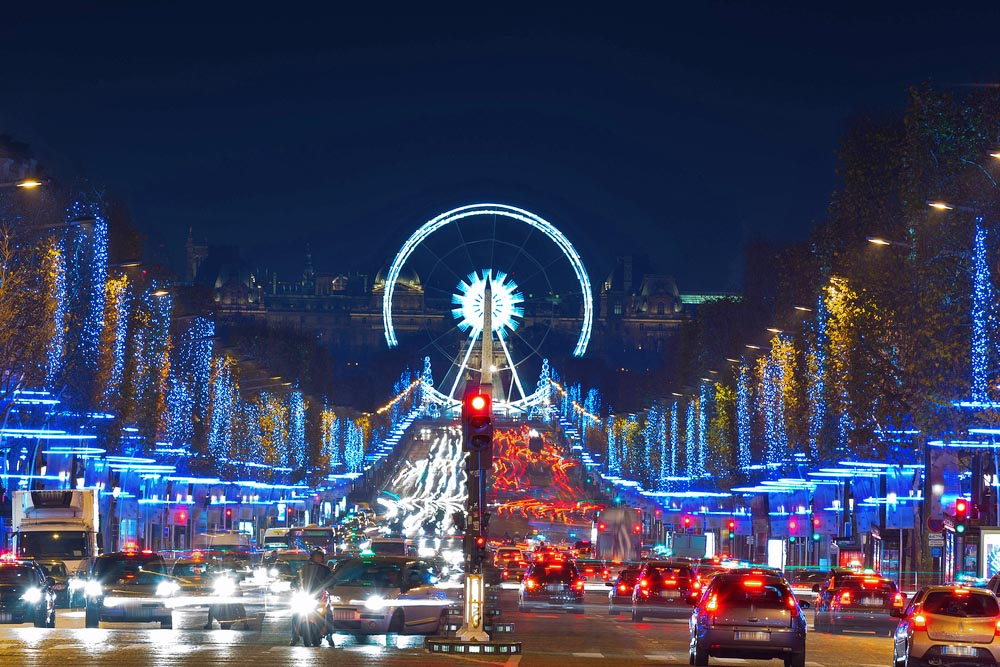 Avenue Champs-Elysees with Christmas illumination and ferris wheel at horizon in Paris. Photo: Shutterstock