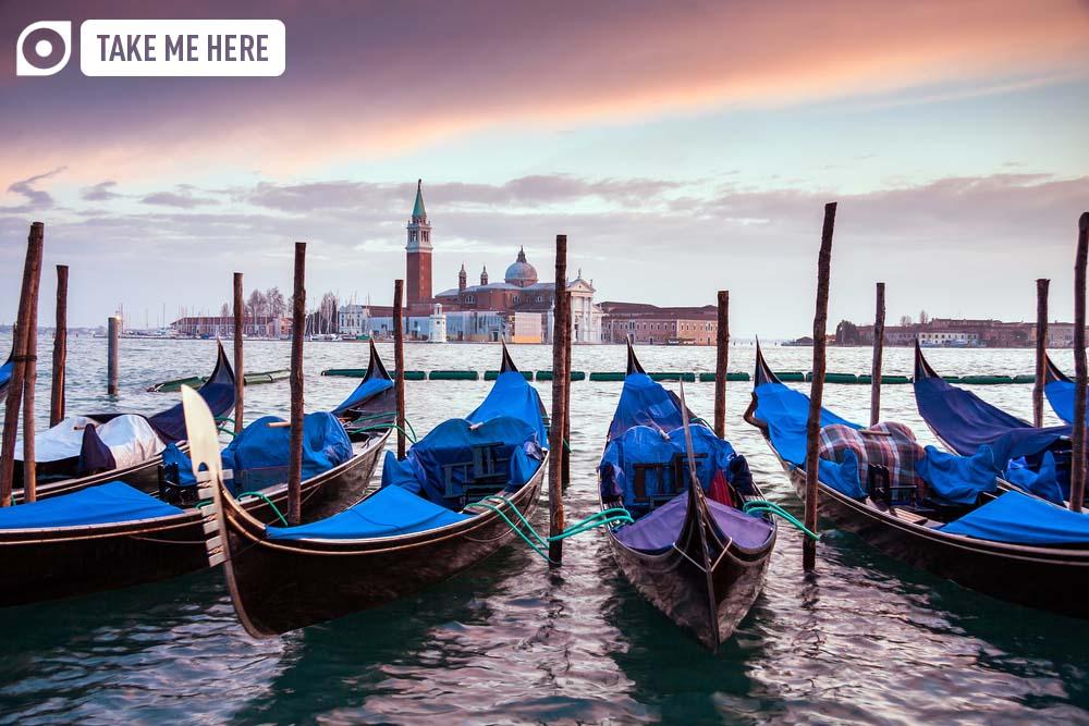 A row of gondolas moored beside the Riva degli Schiavoni in Venice, Italy.