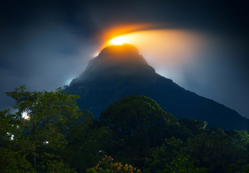 Mountain Adam's Peak (Sri Pada) covered by thick fog highlighted by illumination of the temple. Photo: Shutterstock