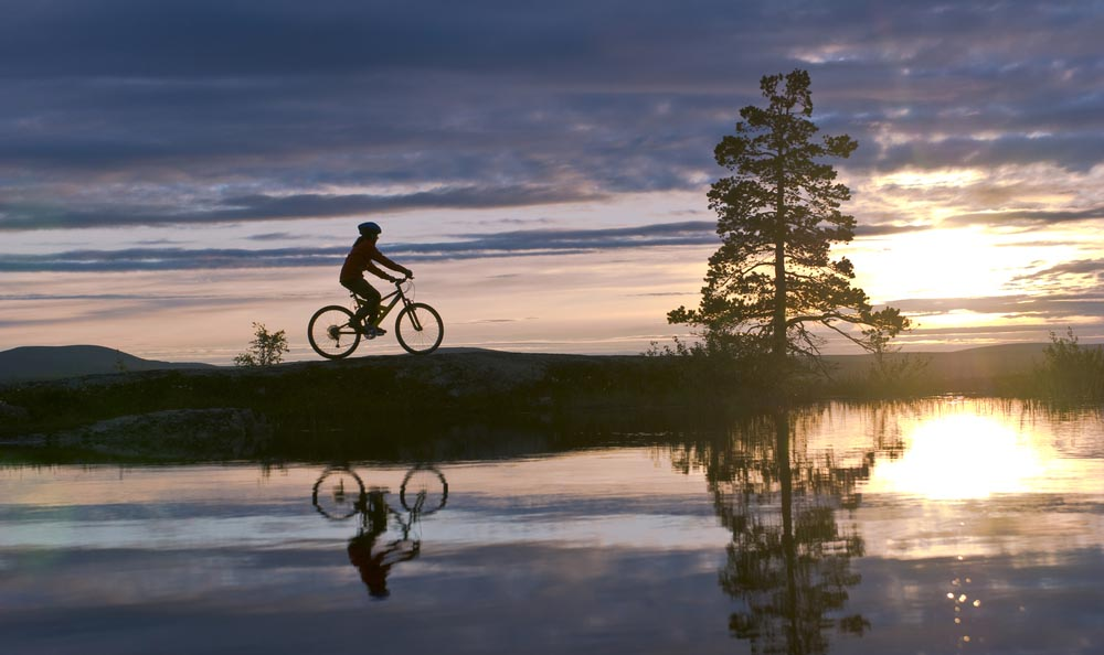 Mountain biker reflected in a Lapland lake.