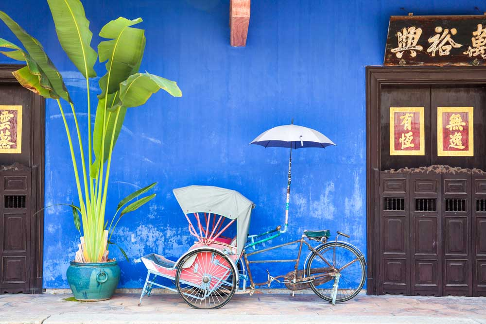 Old rickshaw tricycle near Fatt Tze Mansion or Blue Mansion, famous oriental historical building in Georgetown, Penang, Malaysia. Photo: Shutterstock