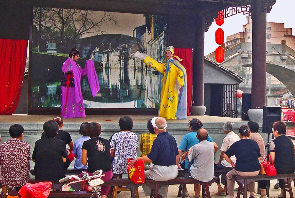 Performance of a chinese drama at a small outdoor theater in Fengjing, water town in surroundings of Shanghai. Photo: Shutterstock