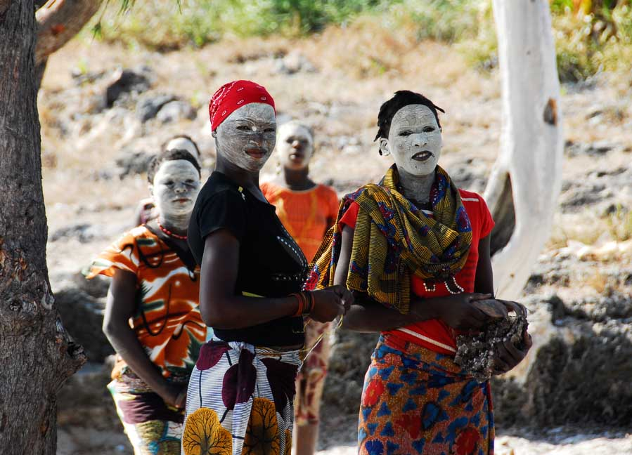 Makua women, with traditional white face mask, welcome a group of tourists in Pangane, Mozambique. Photo: Shutterstock