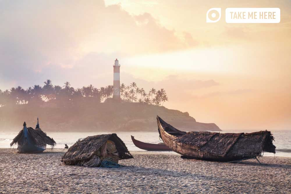 Fisherman boats on the beach in the morning at lighthouse background in Kovalam, Kerala, India. Photo: Shutterstock