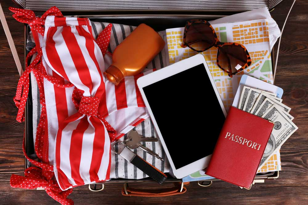 Packed suitcase of vacation items. Photo: Shutterstock