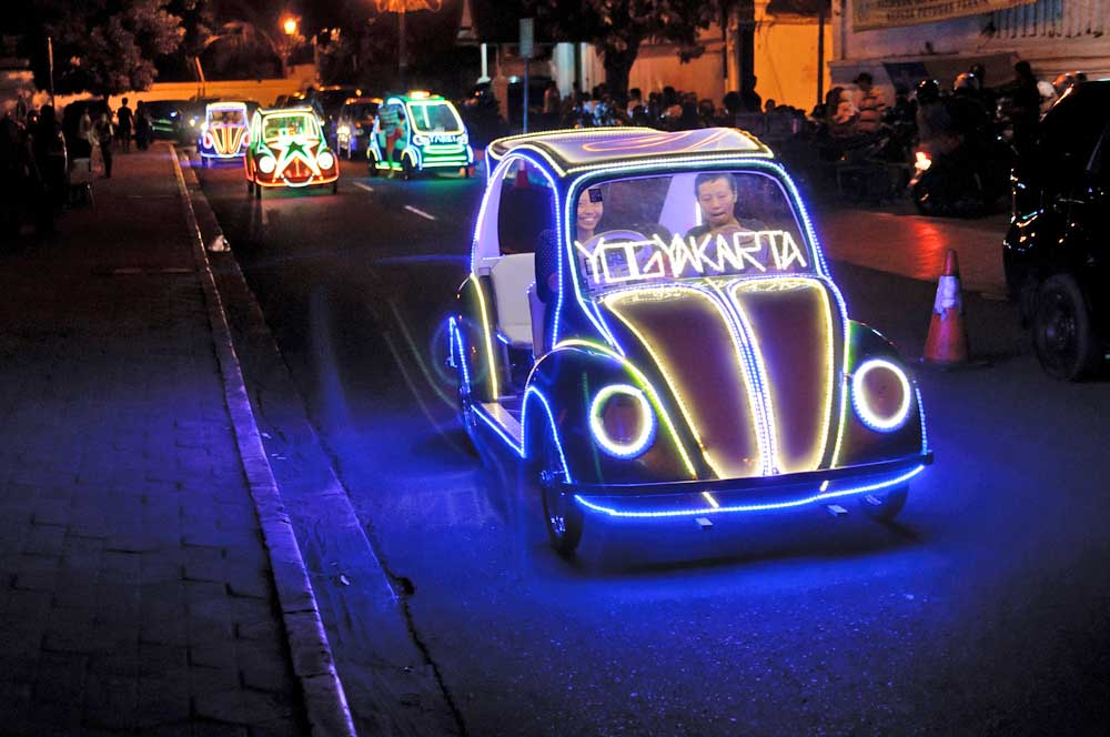 Tourists having fun riding on the illuminated pedal toy cars at night in Yogyakarta, Indonesia. Photo: Shutterstock