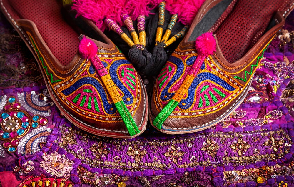Colorful ethnic shoes and camel decorations on violet Rajasthan cushion cover on flea market in Jaipur. Photo: Shutterstock