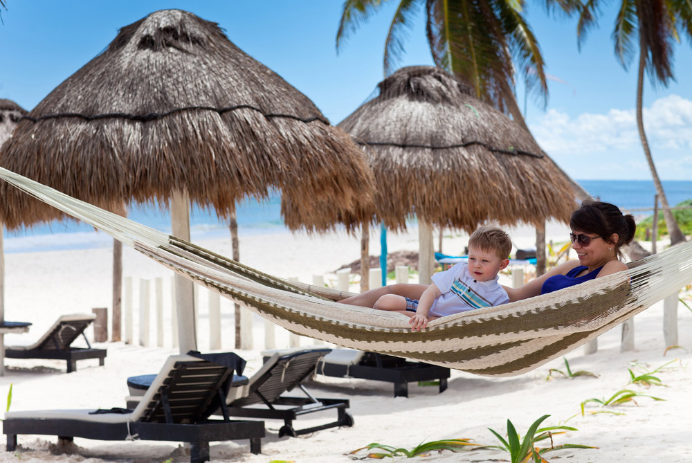 Young mother and son relaxing in a hammock on mexican beach. Photo: Shutterstock