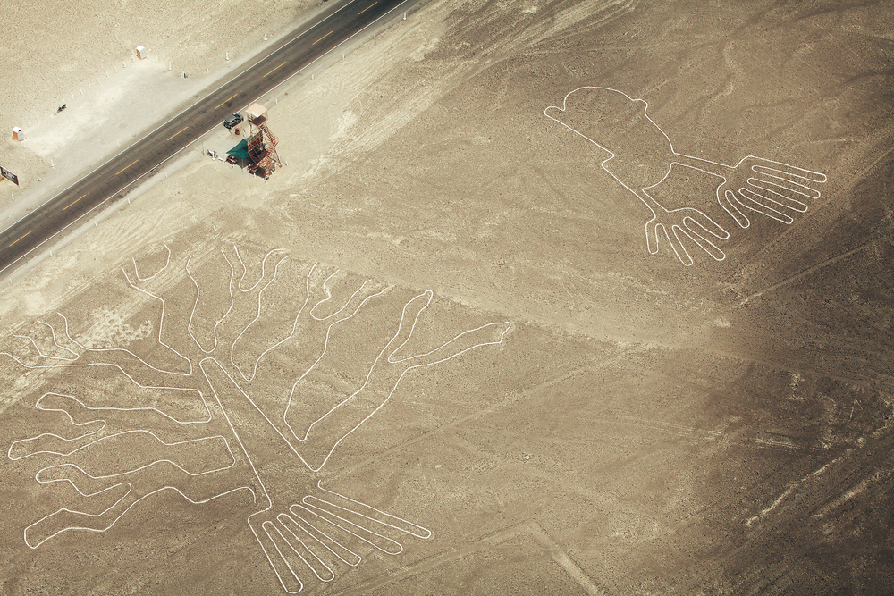 Tree (Arbol) and Hands (Manos) lines in Nazca desert and observation tower near road. Photo: Shutterstock