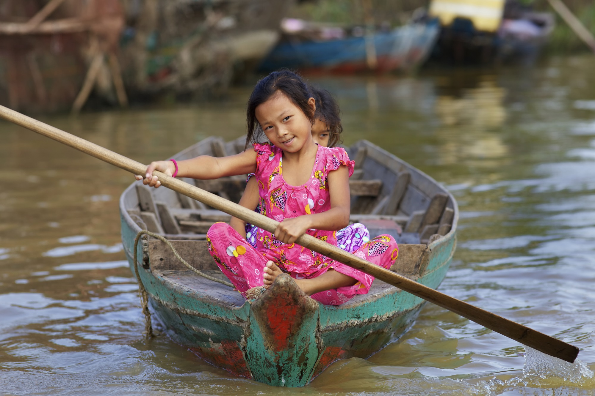 Two children rowing rowing boat on Tonle Sap Lake in Siem Reap, Cambodia. Photo: Stephen Bures / Shutterstock
