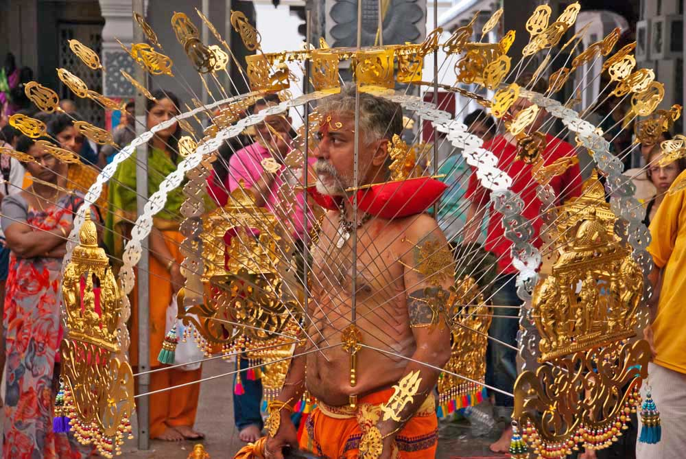 An elder Hindu devotee carries a golden kavadi at Thaipusam in Singapore.