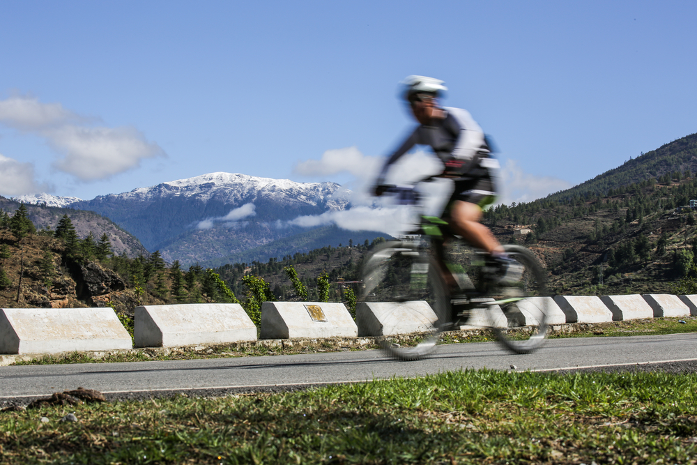 Mountain biking in Bhutan with snow mountain in the background. Photo: Dylan Haskin/Shutterstock