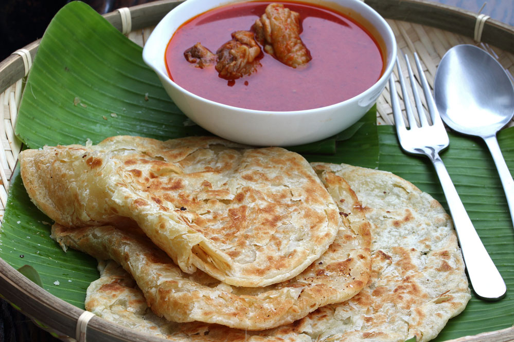 Roti canai with spicy curry on a banana leaf. Photo: Shutterstock