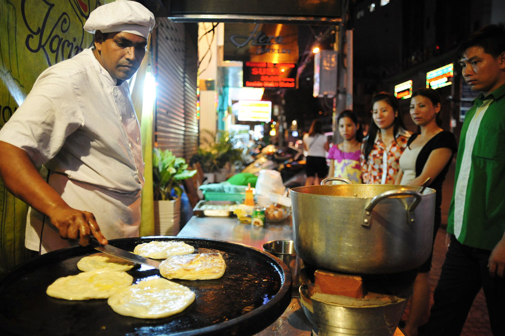 Preparing roti canai for queuing customers. Photo: Shutterstock