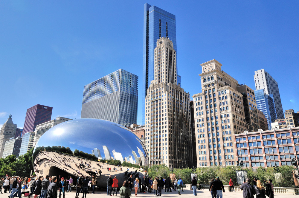 Famous Slivery Bean sculpture in Millennium Park and city buildings in downtown of Chicago. Photo: Shutterstock