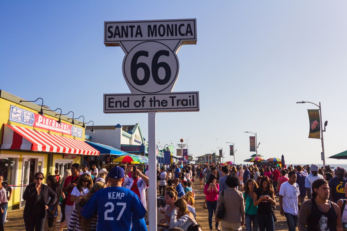 People walking by Santa Monica end of famous Route 66 in Santa Monica Pier. Photo: Razvan Raz/Shutterstock