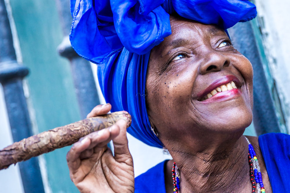 Portrait of african cuban woman smoking cigar in Havana.