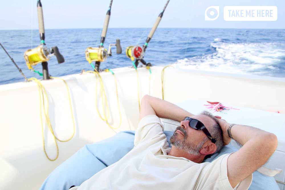 Fisherman relaxing on boat, whilst deep-sea fishing.