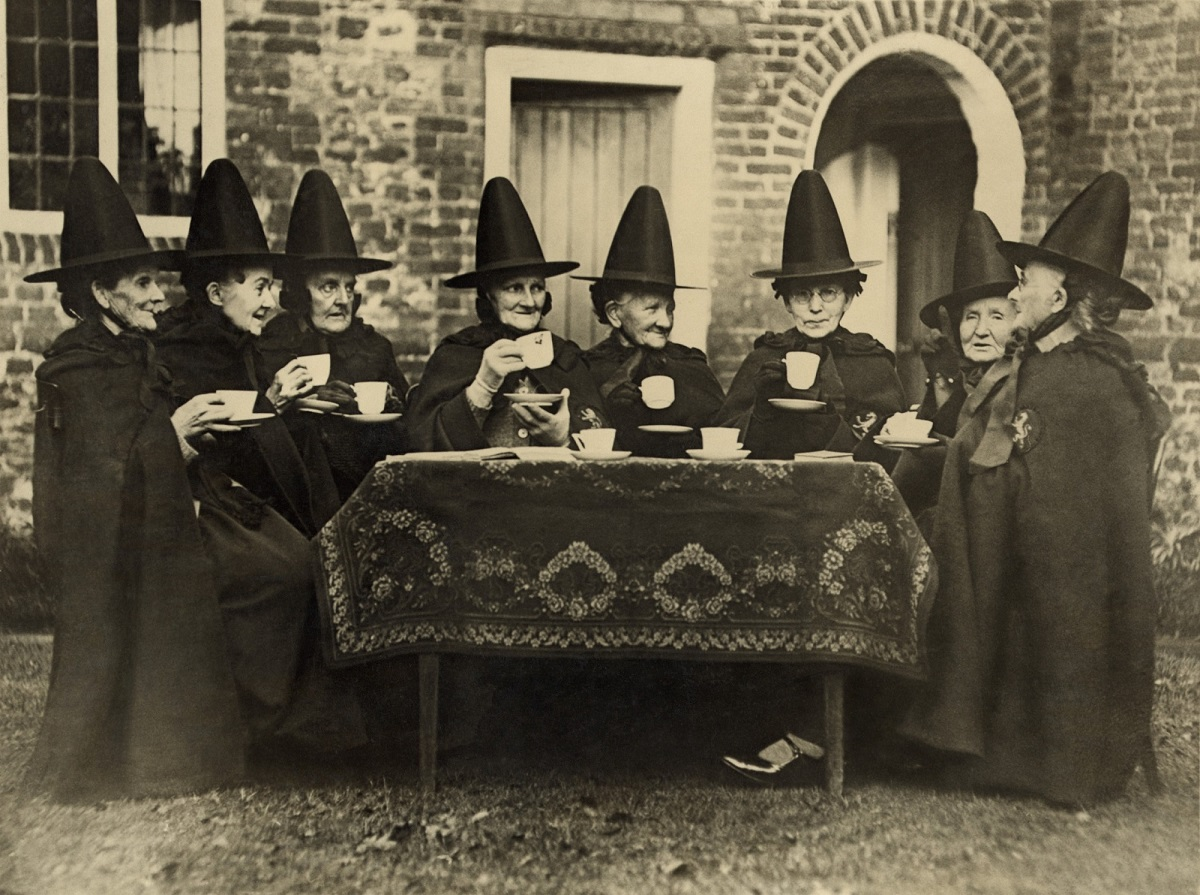 Eight women in high hats having tea. They are not a group of witches but the members of the Holy and Undivided Trinity of Castle Rising, Norfolk, England. Ca. 1920. Photo: Everett Historical/Shutterstock
