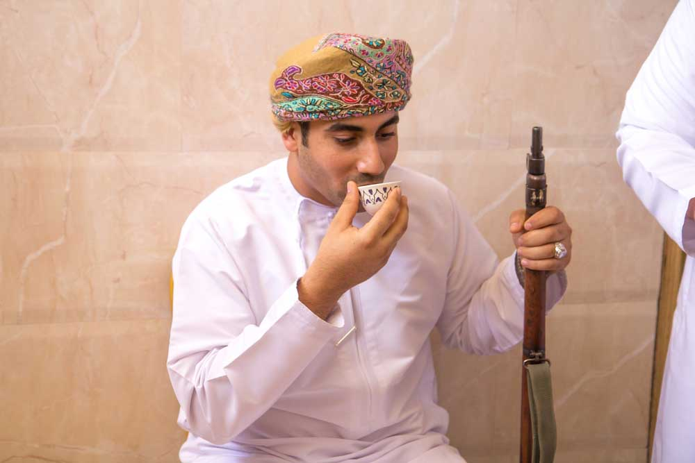 Omani man in traditional clothing posing with his prized weapon while drinking arabic coffee. Photo: Shutterstock