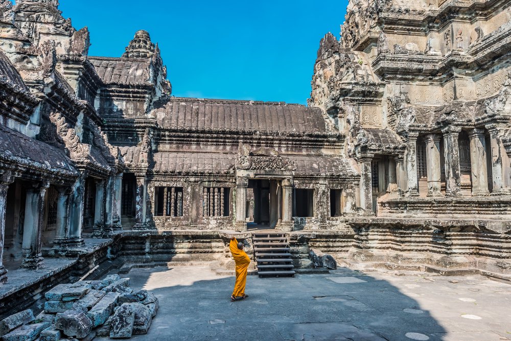 buddhist monk in the temple courtyard at Angkor Wat. Photo: ostill/Shutterstock