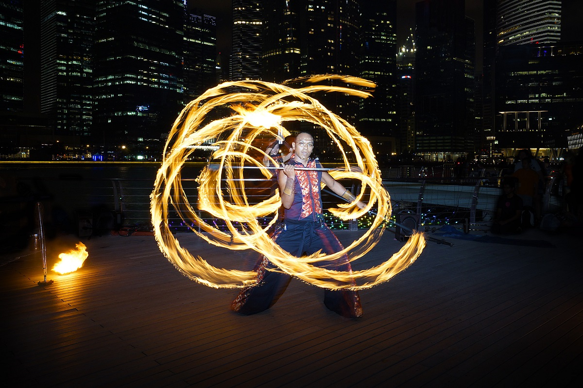 Fire Dancer street performance using fire staff, at Marina Bay. Photo: Jenny Zhang/Shutterstock