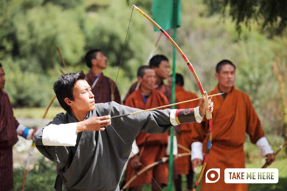 Bhutanese men compete in the national sport of archery at a festival.