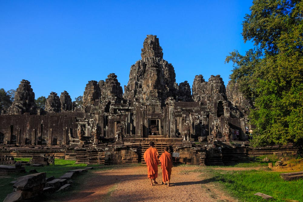 The monks in the ancient stone faces of Bayon temple, Angkor, Cambodia. Photo: Shutterstock