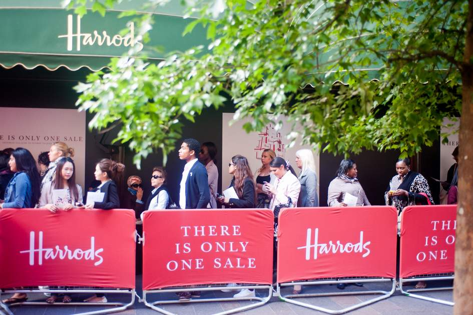 LONDON, UK - JUN 15: customers queue outside the Harrods store in London on June 15, 2013 for the opening of the summer sales.