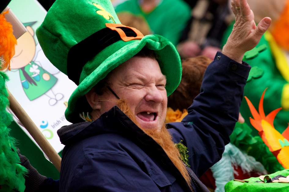 CORK, IRELAND - MARCH 17 - An unidentified man in a St. Patrick's Day parade waving at the crowd wearing a green leprechaun hat and laughing March 17, 2012, Cork, Ireland.