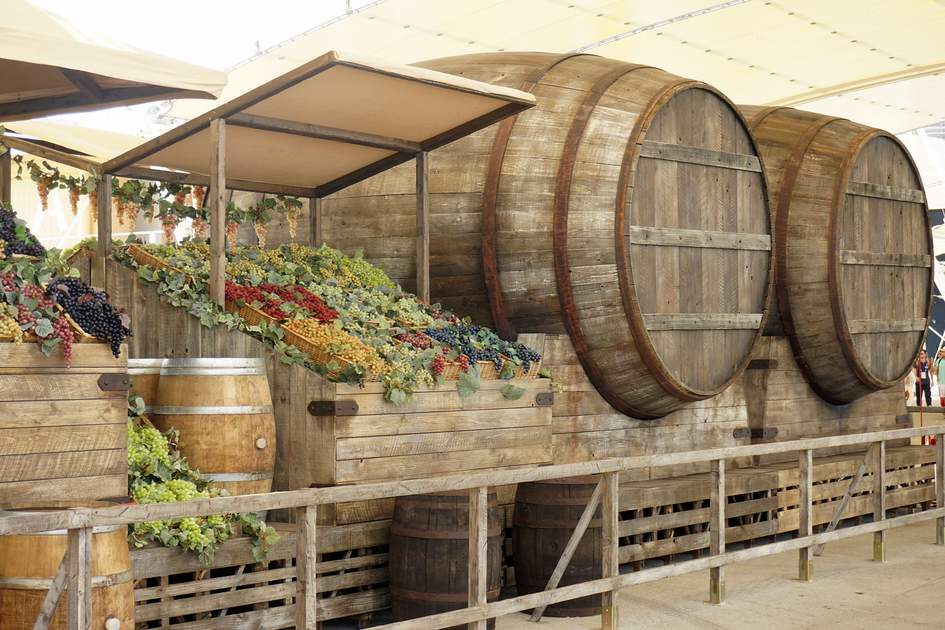 MILAN, ITALY - JULY 8, 2015: reproduction of a wine stand with barrels and grapes along the Decumano main street at Expo 2015, universal exposition on the theme of food in Milan.