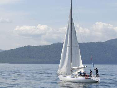 White sailing yacht with some people on board against wooded shore, lake Baikal, Russia
