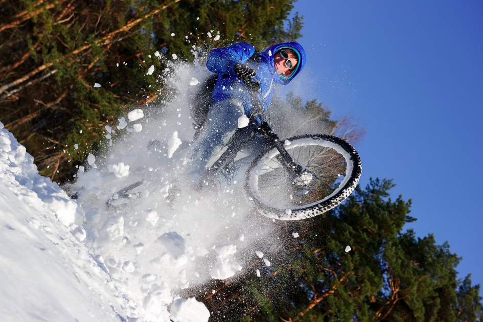 Cyclist riding on a mountain bike in the snow in the winter forest. Photo: Shutterstock