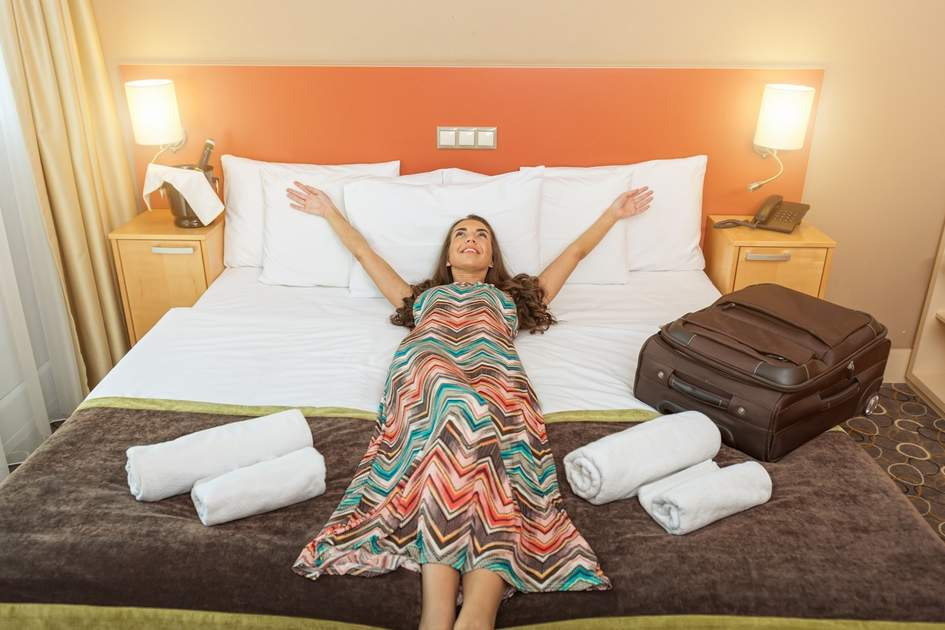 Young woman lying in the bed of a hotel room